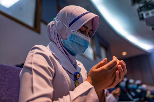 A nurse wears a mask while praying in Selayang, Malaysia. (Getty Images)