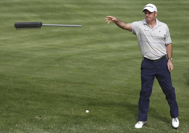 Paul McGinley of Ireland throws a rake to chip onto the 7th hole during the first round of the BMW Masters golf tournament at the Lake Malaren Golf Club in Shanghai, China, Thursday, Oct. 24, 2013. (AP Photo/Eugene Hoshiko)