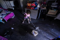 FILE - In this Feb. 23, 2021, file photo, Raella Mills, 3, plays mop-up at her home in Dallas. Raella and her mother's apartment flooded last week by a pipe that burst during the record winter cold. They are still without running water. The snow and ice that crippled some states across the South has melted. But it has exposed the fragility of aging waterworks that experts have been warning about for years. Cities across Texas, Tennessee, Louisiana and Mississippi are still grappling with outages that crippled health care facilities and forced families to wait in line for potable water. (AP Photo/LM Otero, File)