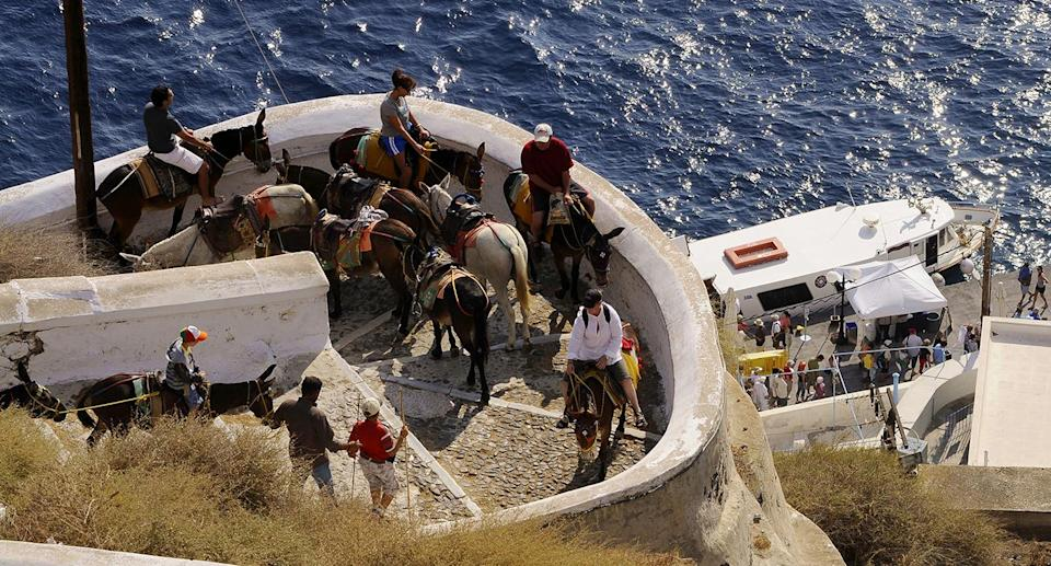 Up to 1,200 tourists visit the small island every day between May and October to take in its beautiful scenery, and many hire donkeys to carry them up to the best viewpoints. Source: Getty