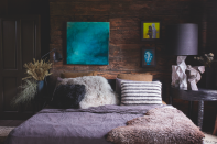 """<p>""""I've clad the wall in wood which I brought from Lassco and then banked the bed up against it. There is something so peaceful about this room, I think it's the use of earthy materials - they feel so restorative. The art is a collection I've picked up on travels, the blue oil painting was a present to ourselves – we lived in the States for three years and the skies, no matter the season, were always blue. When we left I wanting a painting that reminded me of that time and this painting of a forest in twilight does just that. The other two pictures were presents.""""</p>"""