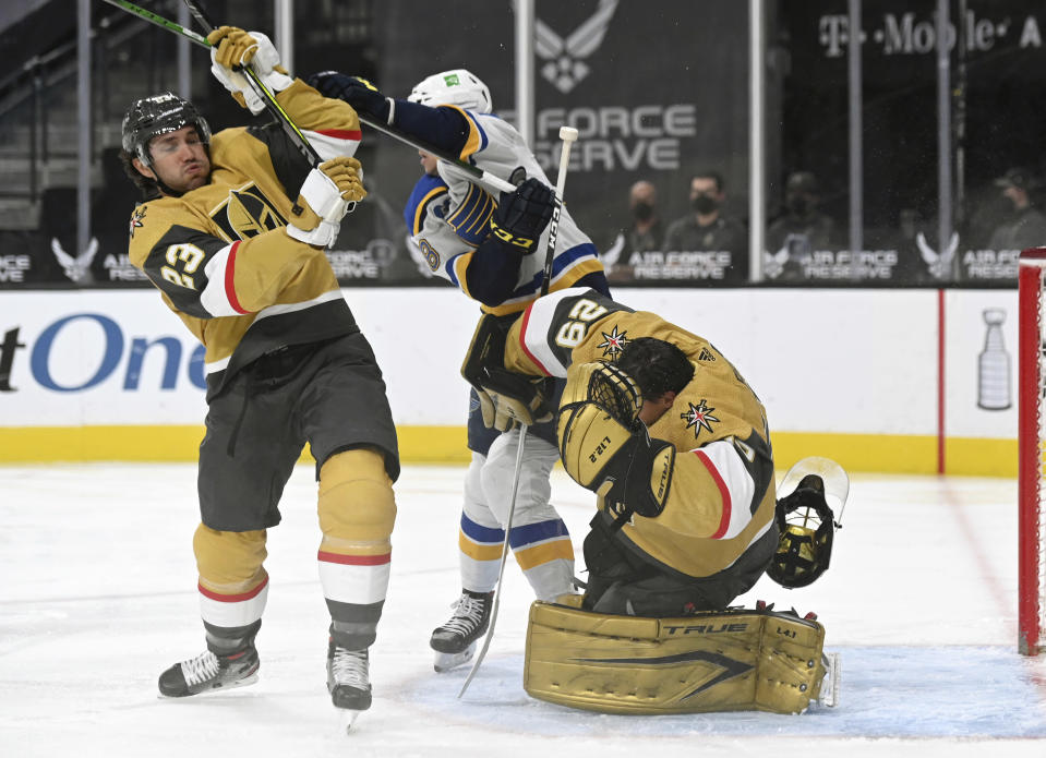Vegas Golden Knights goaltender Marc-Andre Fleury (29) has his helmet knocked off by defenseman Alec Martinez (23) and St. Louis Blues left wing Mackenzie MacEachern (28) during the first period of an NHL hockey game Saturday, May 8, 2021, in Las Vegas. (AP Photo/David Becker)