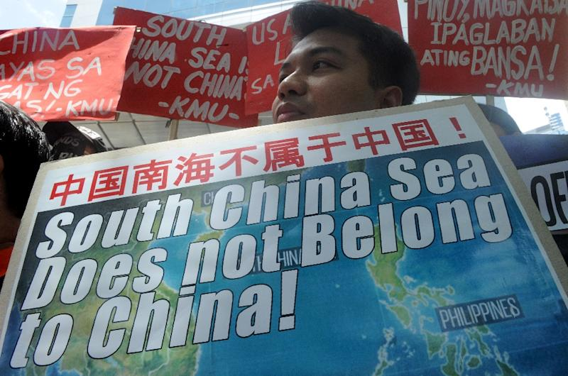 A protestor holds a placard at a rally in front of the Chinese Consulate in Manila's financial district on July 7, 2015, denouncing China's claim to most of the South China Sea including areas claimed by the Philippines (AFP Photo/Jay Directo)