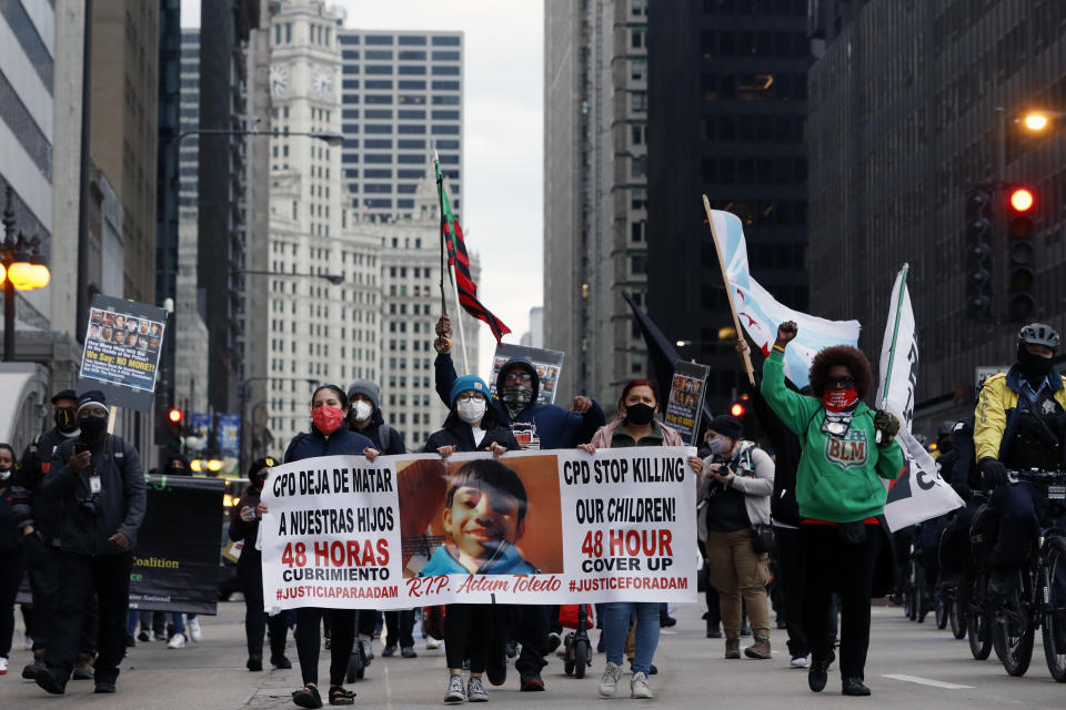 Protesters holding signs navigate along Chicago's South Michigan Avenue during a peaceful protest, Wednesday, April 14, 2021, ahead of the video release of the fatal police shooting of 13-year-old Adam Toledo.