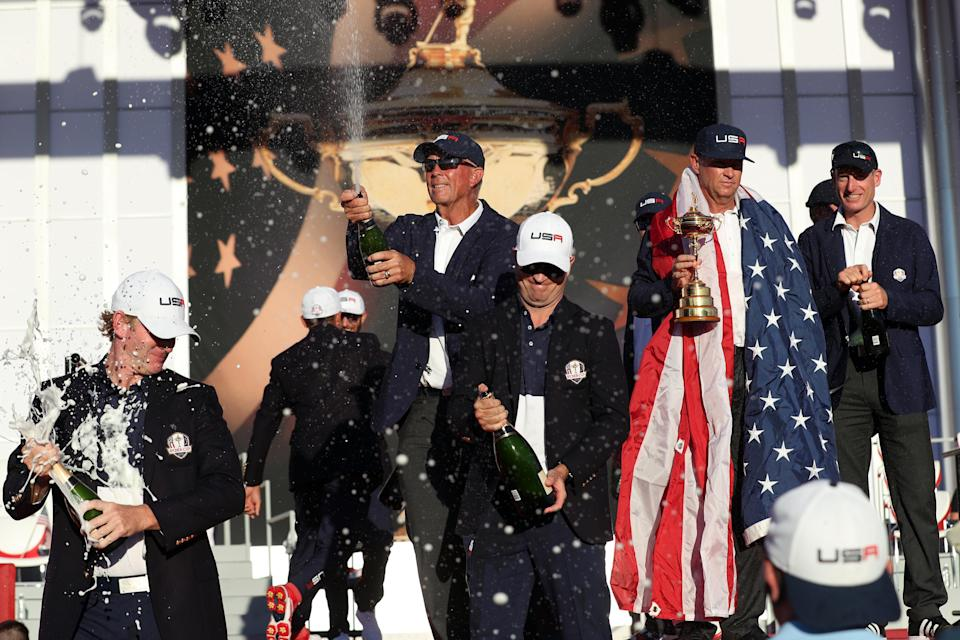 Team USA vice-captain Tom Lehman, Brandt Snedeker and  Zach Johnson spray champagne as Team USA captain Davis Love III celebrates winning with the Ryder Cup.