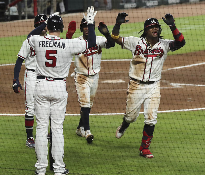 Atlanta Braves Ronald Acuna, right, is greeted at home by Freddie Freeman (5) after he hits a three-run homer for during the fifth inning in a baseball game against the Miami Marlins, Wednesday, Sept. 9, 2020 in Atlanta. (Curtis Compton/Atlanta Journal-Constitution via AP)