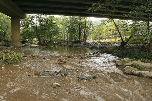<p>Muddy floodwaters of the East Verde River flow under a bridge where one victim of the flash flood was found during a search and rescue operation by the Gila County Sheriff's Office on Sunday, July 16, 2017, in Payson, Ariz. (AP Photo/Ralph Freso) </p>