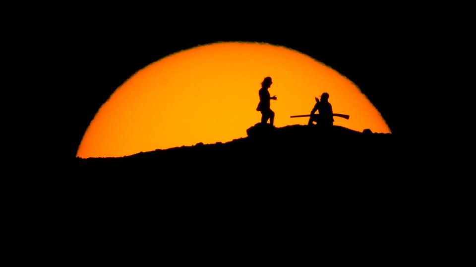 Hikers watch the sunset Saturday from a peak at Papago Park in Phoenix. (Photo: Charlie Riedel/Associated Press)
