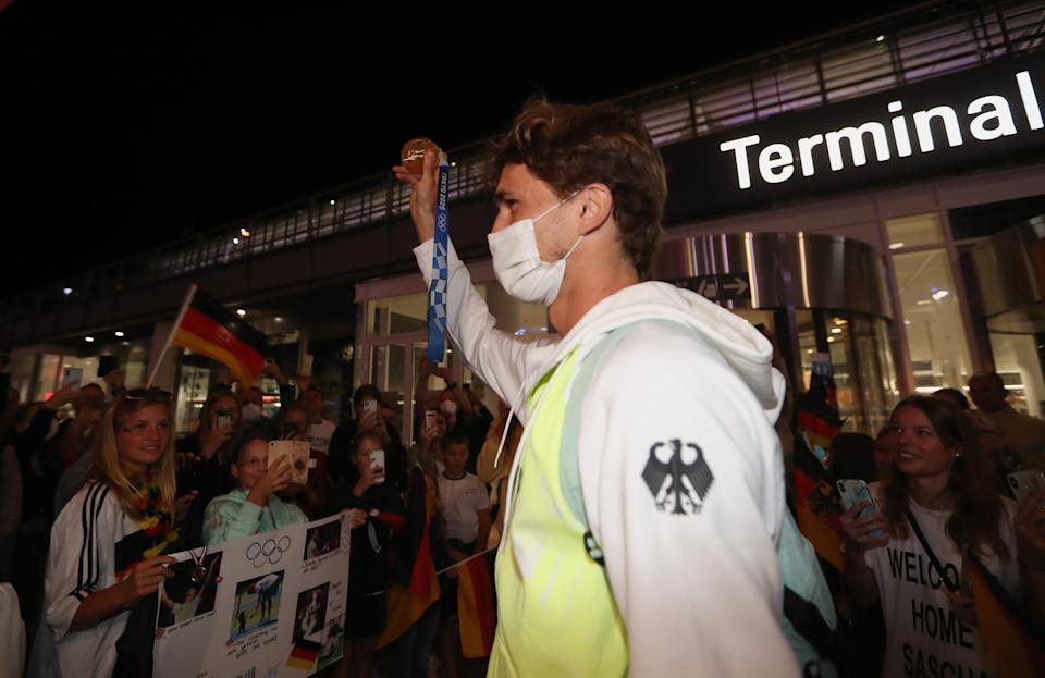 MUNICH, GERMANY - AUGUST 02: German tennis player and Tokyo 2020 gold medalist Alexander Zverev waves showing his gold medal after his arrival at Airport Munich on August 02, 2021 in Munich, Germany. (Photo by Alexandra Beier/Getty Images)