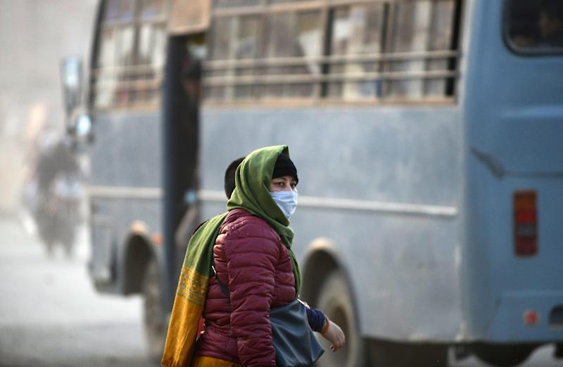 A woman covers her face with a mask as she walks along a dusty road in Kathmandu (AFP Photo/PRAKASH MATHEMA)