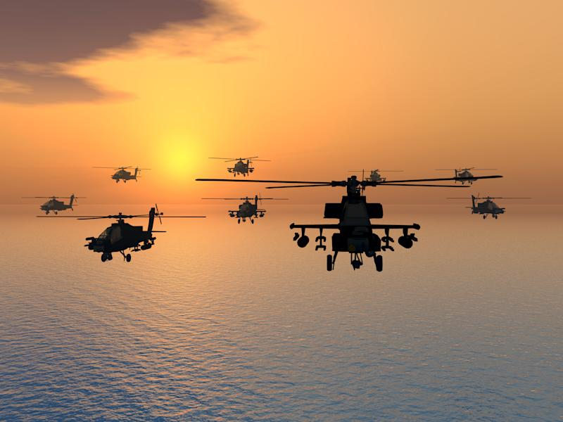 Military helicopters in flight over the ocean