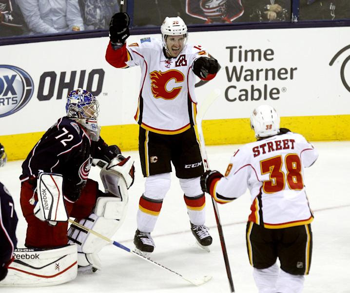 Calgary Flames' Curtis Glencross, center, celebrates with teammate Ben Street, right, after Glencross scored against Columbus Blue Jackets goalie Sergi Bobrovsky, of Russia, in the third period of an NHL hockey game in Columbus, Ohio, Friday, Oct. 4, 2013. Calgary won 4-3. (AP Photo/Paul Vernon)