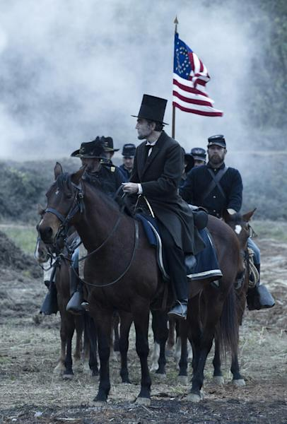 """In this undated publicity photo released by DreamWorks and Twentieth Century Fox, Daniel Day-Lewis, center, as President Abraham Lincoln, looks across a battlefield in the aftermath of a terrible siege in this scene from director Steven Spielberg's drama """"Lincoln."""" (AP Photo/DreamWorks, Twentieth Century Fox, David James)"""