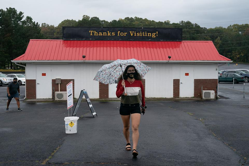 Georgia Tech student Claudia Gomez, 19, arrives at the Gwinnett County Fairgrounds to cast her first ballot on October 24, 2020, in Lawrenceville, Georgia. - Neighbors and volunteers are handing out water and snacks to the masked voters waiting patiently in line to cast their ballots on a hot October day in the Atlanta suburb of Smyrna. Americans go to the polls on November 3 but the enthusiastic early voting here has already given the morning an air of Election Day. Georgia has been a reliably Republican, conservative bastion and a Democrat has not won in the Peach State since Bill Clinton, a fellow Southerner, in 1992. But Democratic candidate Joe Biden, 77, and Republican incumbent Donald Trump, 74, are running neck-and-neck in the polls in Georgia. (Photo by Elijah Nouvelage / AFP) (Photo by ELIJAH NOUVELAGE/AFP via Getty Images)