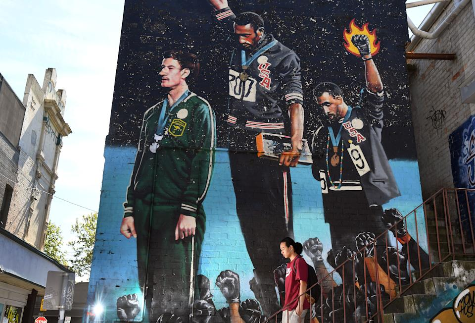 A photo taken in Melbourne on October 8, 2018, shows a man walking past a giant mural of Australian runner Peter Norman with US sprinters Tommie Smith and John Carlos. - When a principled Peter Norman stood on the podium alongside two Americans in their famous Black Power salute at the 1968 Mexico Olympics, his place in the history books was sealed. As sprinters Tommie Smith and John Carlos raised their black-gloved fists in silence, their heads bowed in protest calling for racial equality in the United States, Norman made a choice that lived with him for the rest of his life. (Photo by William WEST / AFP)        (Photo credit should read WILLIAM WEST/AFP via Getty Images)