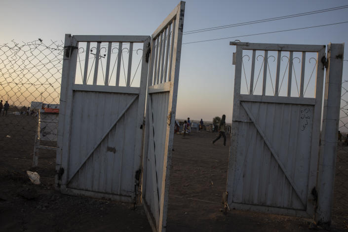 A gate stands open at the Sudanese Red Crescent clinic where surgeon and doctor-turned-refugee, Dr. Tewodros Tefera takes shelter and works in Hamdayet, eastern Sudan, near the border with Ethiopia, on March 22, 2021. (AP Photo/Nariman El-Mofty)