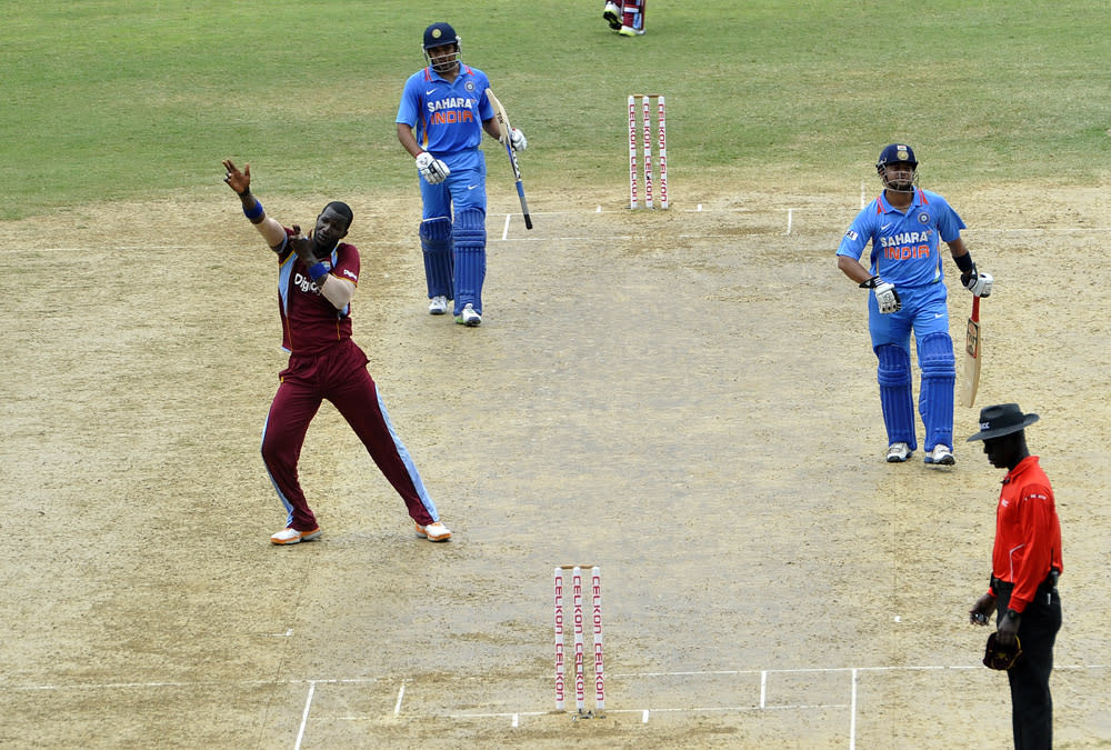 West Indies cricketer Darren Sammy (L) fires an imaginary gun after dismissing Indian batsman Rohit Sharma (C-back) during the second match of the Tri-Nation series between Indian and West Indies at the Sabina Park stadium in Kingston on June 30, 2013. India have scored 229/7 at the end of their innings. AFP Photo/Jewel Samad