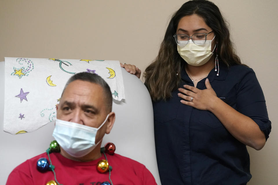 Lummi Nation member James Scott (native name Qwelexwbed), left, waits to receive the first COVID-19 vaccination on the Lummi Reservation as his granddaughter, Mackayla Alvarez, the family's oral historian, looks on to witness the moment, Thursday, Dec. 17, 2020, near Bellingham, Wash. The Native American tribe began rationing its first 300 doses of vaccine as it fights surging cases with a shelter-in-place order. (AP Photo/Elaine Thompson)