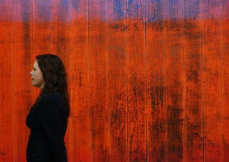 "An employee poses with artist Gerhard Richter's artwork ""Wand (Wall)"" at Sotheby's auction house in London"