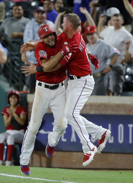 Texas Rangers' Isiah Kiner-Falefa (9) and Scott Heinemann celebrate after Kiner-Falefa hit a run-scoring single in the 11th inning of a baseball game against the Los Angeles Angels in Arlington, Texas, Monday, Aug. 19, 2019. The Rangers won 8-7. (AP Photo/Tony Gutierrez)