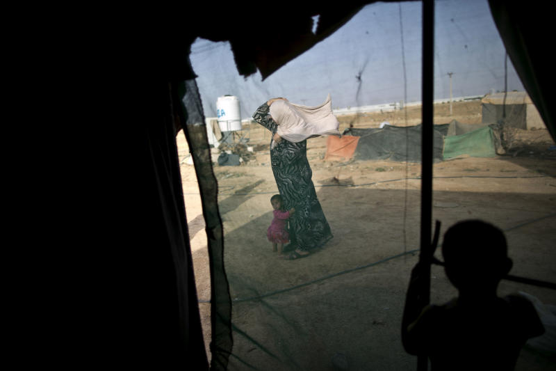 FILE -- In this June 3, 2016 file photo, a Syrian refugee holds on to her headscarf against the wind while she and her daughter stand outside their tent at an informal tented settlement near the Syrian border, on the outskirts of Mafraq, Jordan. Nearly a year after Jordan opened its main border crossing for Syrian refugees to go home, few are taking up the offer. Afraid to return home, unable to earn a decent living in Jordan and unwanted by the West, refugees are trapped in a cycle of poverty and debt while straining the resources of a country that is already struggling to meet the needs of its own population. (AP Photo/Muhammed Muheisen, File)
