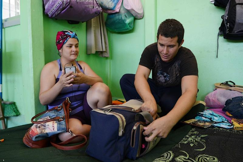 A Cuban couple pack their belongings in a shelter in La Cruz, Costa Rica, on January 12, 2016, before trying to reach the United States, hoping to make a new life there (AFP Photo/Carlos Gonzalez)