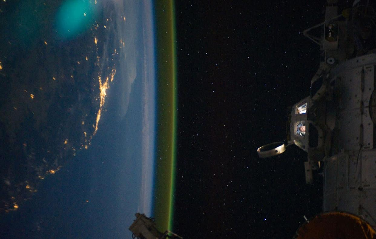This unique photographic angle, featuring the International Space Station's Cupola and crew activity inside it, other hardware belonging to the station, city lights on Earth and airglow was captured by one of the Expedition 28 crew members. The major urban area on the coast is Brisbane, Australia. The station was passing over an area southwest of Canberra.