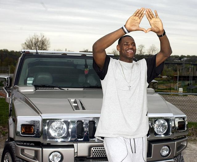 "<a class=""link rapid-noclick-resp"" href=""/nba/players/3704/"" data-ylk=""slk:LeBron James"">LeBron James</a> poses in front of his Hummer after declaring for the NBA draft in April 2003. (AP)"