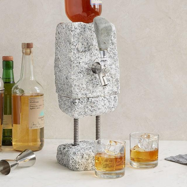 """<h2>Uncommon Goods Stone Drink Dispenser</h2><br>Most orders leave the Uncommon Goods warehouse within two to five business days, but we suggest cashing in on some expedited shipping for this showstopping cobbled granite drink dispenser. <br><br><em>Shop</em> <strong><em><a href=""""http://uncommongoods.com"""" rel=""""nofollow noopener"""" target=""""_blank"""" data-ylk=""""slk:Uncommon Goods"""" class=""""link rapid-noclick-resp"""">Uncommon Goods</a></em></strong><br><br><strong>Uncommon Goods</strong> Stone Drink Dispenser, $, available at <a href=""""https://go.skimresources.com/?id=30283X879131&url=https%3A%2F%2Fwww.uncommongoods.com%2Fproduct%2Fstone-drink-dispenser"""" rel=""""nofollow noopener"""" target=""""_blank"""" data-ylk=""""slk:Uncommon Goods"""" class=""""link rapid-noclick-resp"""">Uncommon Goods</a>"""
