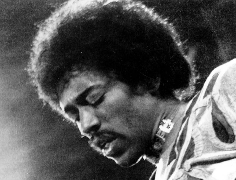 """FILE- In this 1970 file photo, Jimi Hendrix performs on the Isle of Wight in England. A new Jimi Hendrix album is coming March 5. The musician's website says """"People, Hell and Angels"""" contains 12 previously unreleased tracks recorded in 1968 and '69. Rolling Stone revealed the album cover on its website Wednesday, Nov. 21, 2012.(AP Photo/file)"""