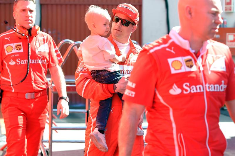 Ferrari's Finnish driver Kimi Raikkonen (2ndR) holds his son Robin in his arms at the Circuit de Catalunya on March 10, 2017 in Montmelo on the outskirts of Barcelona on the fourth day of the second week of tests ahead of the Formula One Grand Prix season. / AFP PHOTO / LLUIS GENE (Photo credit should read LLUIS GENE/AFP via Getty Images)