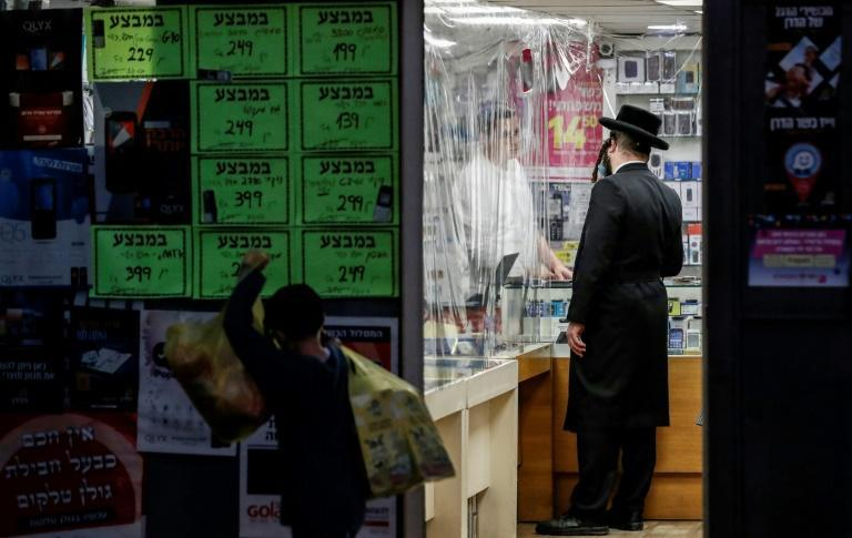 An ultra-Orthodox Jewish man, mask-clad due to the Covid-19 pandemic, inquires about a product at a shop in Jerusalem