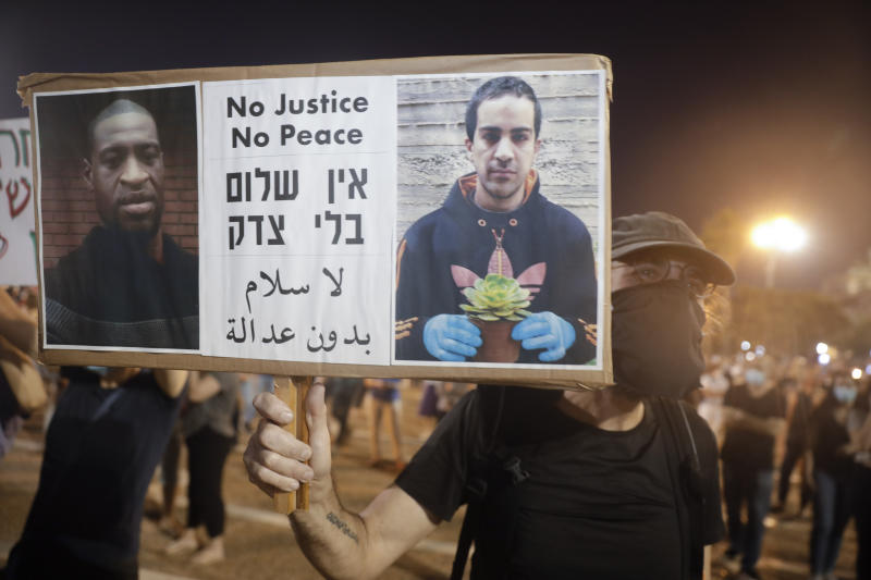 Protesters attend a rally against Israel plans to annex parts of the West Bank, in Tel Aviv, Israel, Saturday, June 6, 2020. Protester holds a portrait of Eyad Hallaq, on the right, a Palestinian with severe autism who was killed recently by Israeli border police officers after a chase in Jerusalem's Old City after apparently being mistaken as an attacker, and George Floyd who was killed during a police arrest in Minneapolis, Minnesota, May 25, 2020. (AP Photo/Sebastian Scheiner)