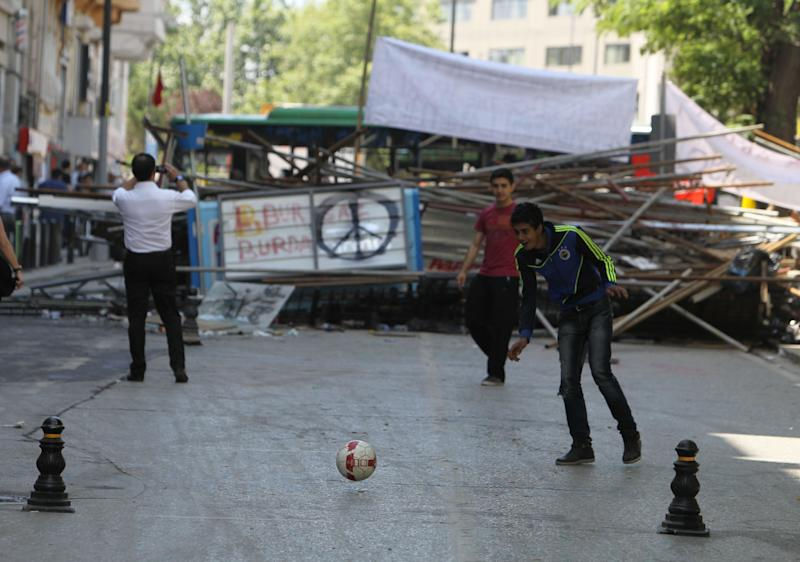 Protesters play soccer next to a barricade at the Gezi park of Taksim in Istanbul, Turkey, Thursday, June 6, 2013. The reasons behind Turkey's eight day of protests are serious enough. But demonstrators have also reacted with humor, particularly on social media sites, often lampooning the prime minister and poking fun at his comments. (AP Photo/Thanassis Stavrakis)