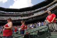 Fans stand during a moment of silence observed by the Texas Rangers and Seattle Mariners in remembrance of those killed in the shootings in Odessa, Texas, before a baseball game between the two clubs in Arlington, Texas, Sunday, Sept. 1, 2019. (AP Photo/Tony Gutierrez)