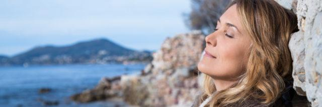 Blonde woman with her eyes closed leaning against a wall at the beach with the ocean and mountains in the background