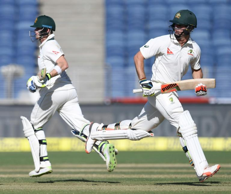 Australia's captain Steve Smith (L) and Mitchell Marsh run between the wickets during the second day of the first  Test against India in Pune in February