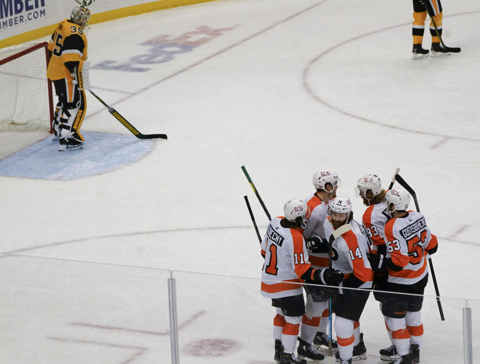 Philadelphia Flyers' Sean Couturier (14) celebrates with teammates after scoring against Pittsburgh Penguins goaltender Tristan Jarry (35) during the first period of an NHL hockey game Thursday, March 4, 2021, in Pittsburgh. (AP Photo/Keith Srakocic)