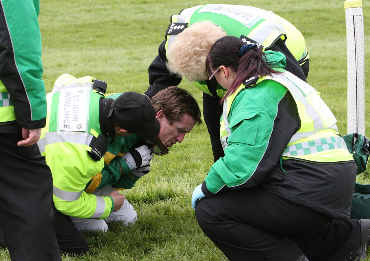 AP McCoy is treated by paramedics after falling from Synchronized at Becher's Brook during the Grand National horse race at Aintree Racecourse, Liverpool, England, Saturday April 14, 2012. (AP Photo/Scott Heppell)