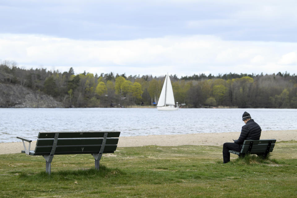 A man sits alone on a bench on the beach of lake Malaren, during the coronavirus outbreak in Satra south east of Stockholm, Saturday, April 25, 2020. (Henrik Montgomery/TT News Agency via AP)