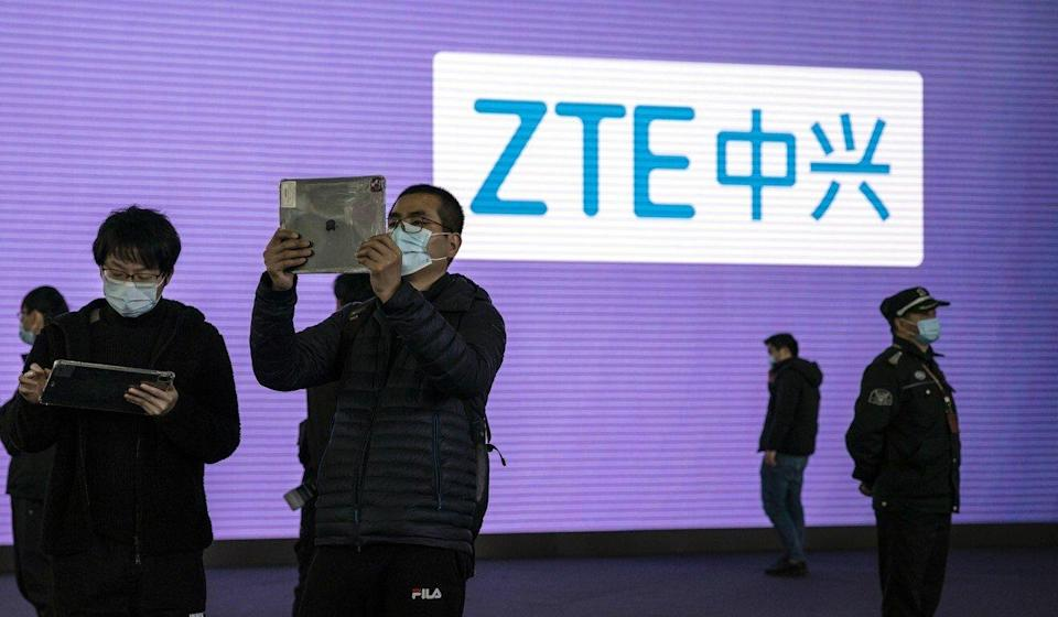 Attendees use tablets in front of signage for ZTE at a technology conference in Shanghai, China in February. Photo: Bloomberg