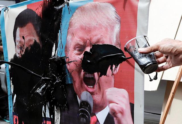 <p>Protesters smear images of President Donald Trump and Philippine President Rodrigo Duterte with paint during a rally against the U.S. President's visit near the U.S. Embassy, in Manila, Philippines Nov. 10, 2017. (Photo: Erik De Castro/Reuters) </p>