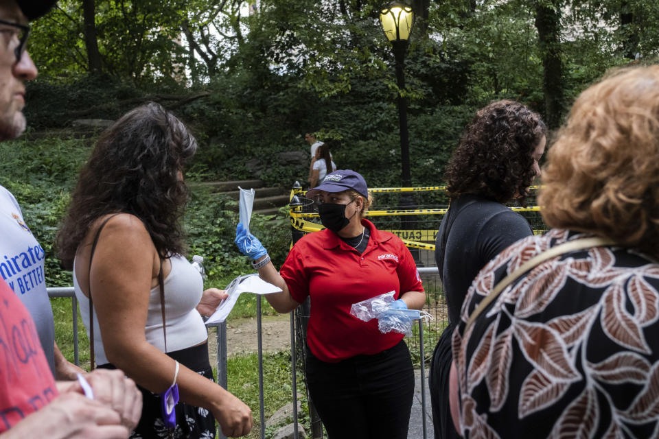 """A staff distributes free masks before the """"We Love NYC: The Homecoming Concert"""" in New York's Central Park, Saturday, Aug. 21, 2021. We Love NYC, The Homecoming Concert celebrate its recovery from the coronavirus pandemic despite surging cases and hospitalizations due to the delta variant. (AP Photo/Jeenah Moon)"""