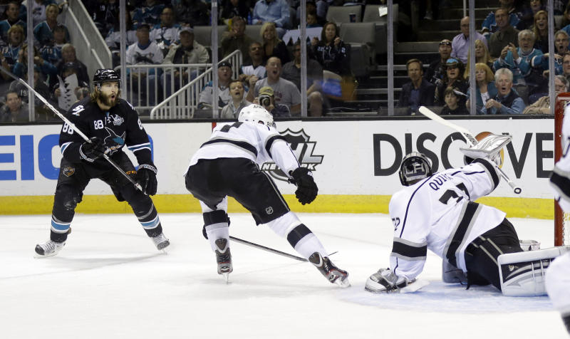 San Jose Sharks' Brent Burns, left, scores past Los Angeles Kings goalie Jonathan Quick, right, during the first period in Game 4 of their second-round NHL hockey Stanley Cup playoff series in San Jose, Calif., Tuesday, May 21, 2013. (AP Photo/Marcio Jose Sanchez)
