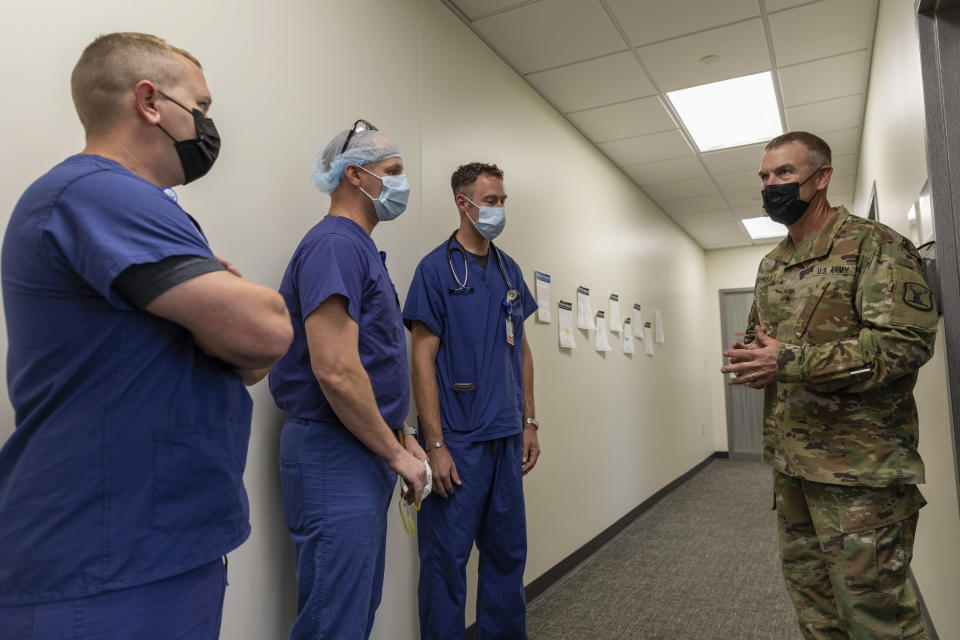 In this photo provided by the Defense Visual Information Distribution Service, Idaho National Guard Brig. Gen. Russell Johnson, the dual-status commander for the state of Idaho, speaks with members of the U.S. Army medical team during response operations at Kootenai Health regional medical center in Coeur d'Alene, Idaho,on Sept. 6, 2021. Kids in Coeur d'Alene were getting ready for their first day of school when Idaho public health officials announced this week that northern hospitals were so crowded with coronavirus patients that they would be allowed to ration health care. Kootenai Health has had to move some patients into a conference room and get help from the military to deal with the flood of coronavirus patients. (Sgt. Kaden D. Pitt/DVIDS U.S. Army via AP)