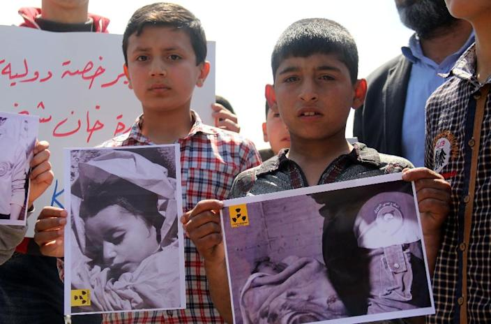 Residents of Khan Sheikhun hold placards and pictures on April 7, 2017, during a protest condemning a suspected chemical weapons attack on their town that killed at least 86 people, among them 30 children (AFP Photo/Omar haj kadour)