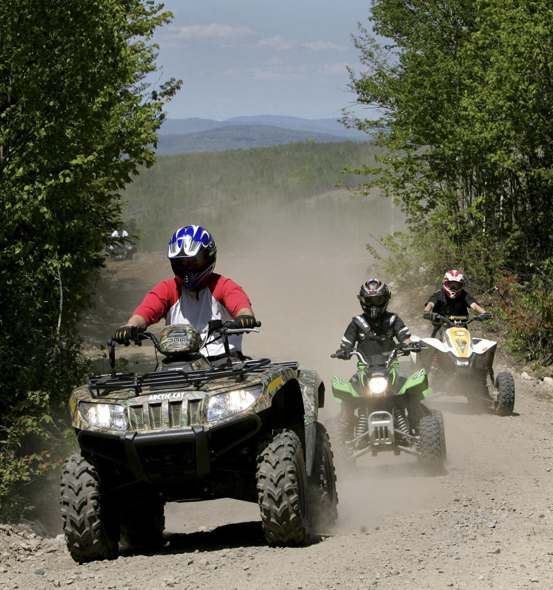 "FILE -  In this Sunday, May 23, 2010 file photo, Jude Stohl leads Leigha Cicchetto and his son Ethan Stohl on a ride through Jericho Park's trail system in Berlin, N.H. In New Hampshire, a new interconnected all-terrain vehicle trail system dubbed ""Ride the Wilds"" will officially open June 15, 2013, capping years of work by more than a dozen off-road vehicle clubs who worked with state agencies and local communities to link 1,000 miles of trails across Coos County. (AP Photo/Jim Cole, File)"