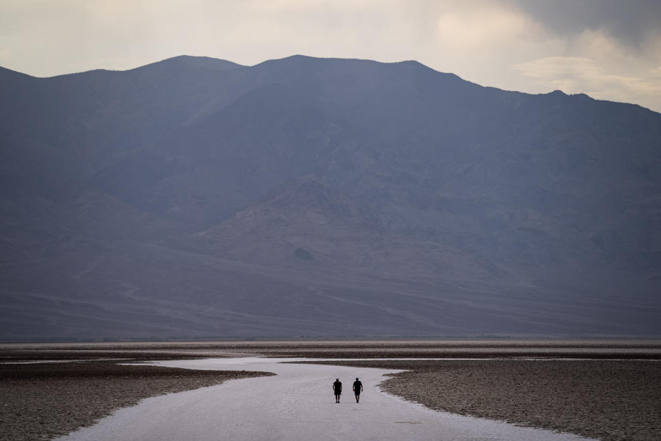 People walk on salt flats in Badwater Basin, Sunday, July 11, 2021, in Death Valley National Park, Calif. Death Valley, in southeastern California's Mojave Desert, reached 128 degrees Fahrenheit (53 Celsius) on Saturday, according to the National Weather Service's reading at Furnace Creek. The previous day's temperature reached 130 F (54 C). (AP Photo/John Locher)