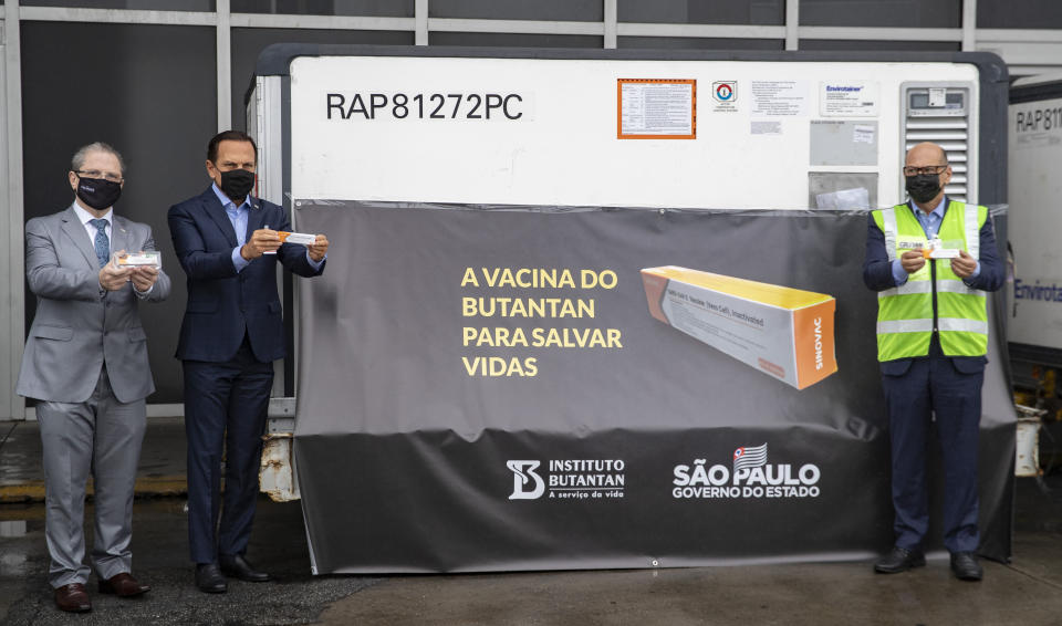 Sao Paulo Governor Joao Doria, second from left, Sao Paulo state Health Secretary Dr. Jean Gorinchteyn, far left, and Butantan Institute Director Dimas Covas, right, pose for photos next to a container carrying the experimental COVID-19 vaccine CoronaVac after it was unloaded from a cargo plane that arrived from China at Guarulhos International Airport in Guarulhos, near Sao Paulo, Brazil, Thursday, Nov. 19, 2020. The experimental vaccine is being tested in a partnership with the Butantan Institute and Chinese pharmaceutical company Sinovac. (AP Photo/Andre Penner)