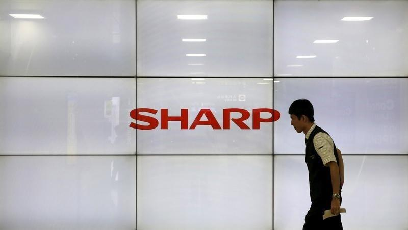 A man walks past display showing a logo of Sharp Corp in Tokyo